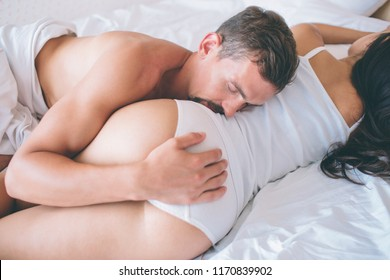 Sexy and absolute stunning picture of couple lying together in bed. Guy holds hand on girl's buttocks and touching her hips with head. Guy is sleeping. And girl as well.