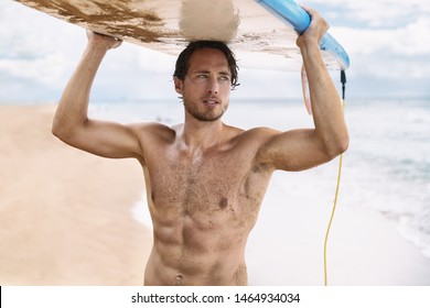 Sexy active watersport fitness abs man carrying his surfboard on the head. Surfer lifestyle on Hawaii beach during summer travel vacation. Caucasian athlete going out surfing holding surf board.