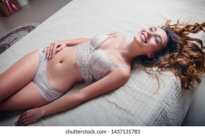Sexy adorable smiling girl in underwear lying on a bed. Portrait of sensual young woman in lingerie