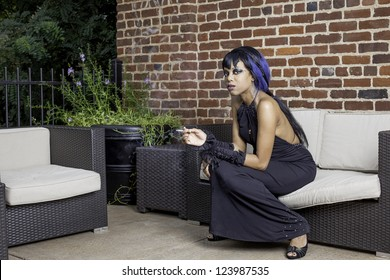 Sexy african american gothic woman smoking. Sitting on a couch outdoor patio, space for text.