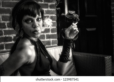 Sexy african american gothic woman smoking. Creative, dramatic lighting with smoke, sexy eyes, seductive look, black and white photo