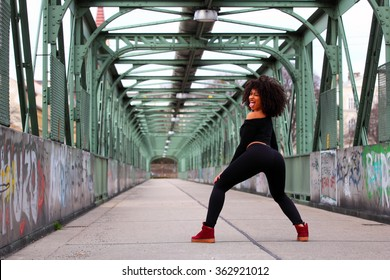 Sexy African dancehall dancer on a bridge