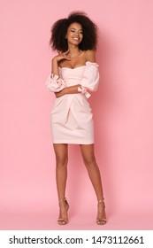 Sexy afro-amerikanisches Modell in rosafarbenem Mini-Kleid einzeln auf rosafarbenem Hintergrund.