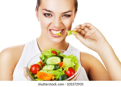 sexy agressive woman biting salad on white background