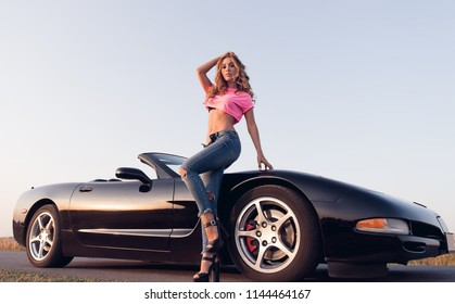 Sexy alluring young girl dressed in jeans and topic standing at the car (cabriolet). Outdoor portrait on the road at sunset