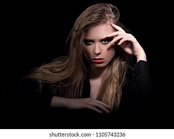 Sexy angry glamour female model with long blond hair posing in black shirt on dark black background with red lipstick. Art portrait. Vogue