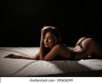 Sexy, appealing and beautiful young woman with slim hot body and tanned skin is posing in the erotic black lacy underwear in the studio on the white sheets, dark background. Girl in the lingerie