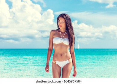 Sexy asian beach model woman beauty showing off toned abs and slim bikini body on tropical caribbean travel vacation. Girl with tanned skin and white fashion swimsuit.