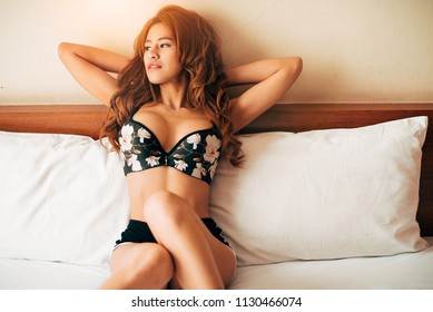 Sexy Asian beautiful woman in bed lingerie with sunset Portrait of attractive young women.