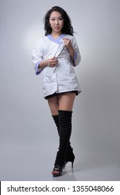 Sexy asian female nurse in white uniform on light background