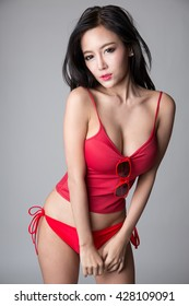 Sexy asian girl wearing red shirt and red panties, posing with sunglasses