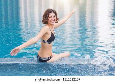 sexy asian lady in swimming suite posting water pool. Relax in holiday concept