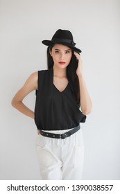 Sexy Asian model woman in black shirt and white pants, wearing hat, standing and posing, studio shot on white background.