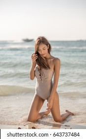 sexy asian woman in bikini one piece suit on the beach