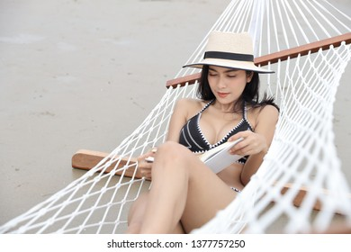 sexy asian woman in black and white bikini who lying on hammock and reading book on sandy beach with beauty face on vacation during summer time