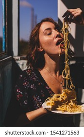 Sexy asian woman in italian style eating spaghetti with her hands. Curly brunette woman wear black floral dress. Sexy kitchen. Woman hold plate with spaghetti. Sexy kitchen. Redhead girl with freckles