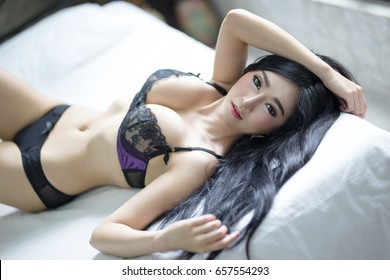 Sexy asian woman in lingerie, posing in her bed