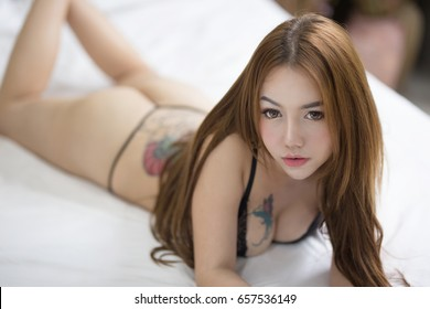 Sexy asian woman in lingerie and thong lying on the bed.