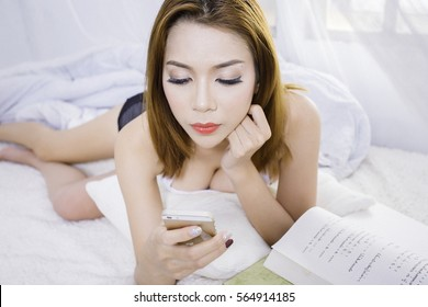 Sexy Asian woman play mobile on bed.