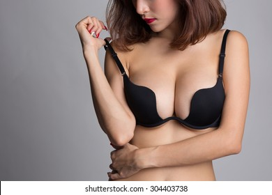 Sexy asian woman showing her breast in black bra or lingerie