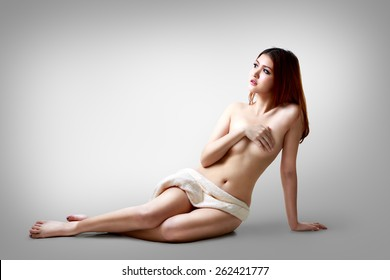 Sexy asian woman sitting on the floor, Isolated on grey background
