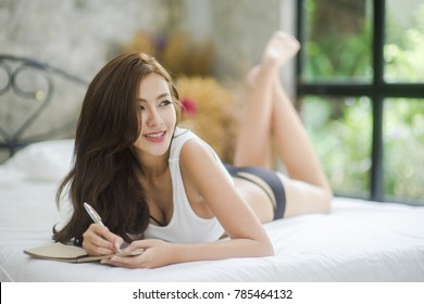 Sexy Asian Woman writing diary On Bed At Home