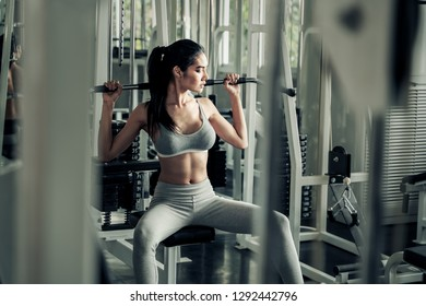 Sexy asian women exercising with a lat pulldown machine to play the arms and shoulder muscles in the gym. Exercise in the gym concept.