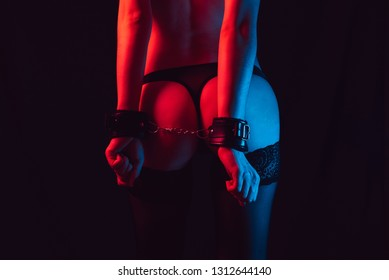 sexy ass girl with handcuffs in thongs and stockings with erotic slender body and figure. BDSM toys for role-playing games with submission and domination in sex