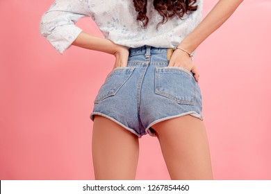 Sexy ass in jeans sweet style, slender clothes ass in pants. Sexy woman body in jeans shorts. Slim Model on back side. Studio shot on pink background.