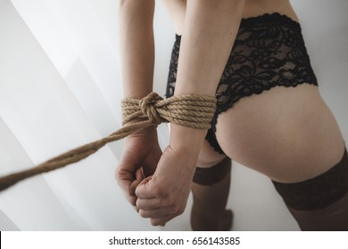 Sexy ass of a young beautiful woman with her hand tied with black bead behind her back. Bdsm. Shibari. Bandage
