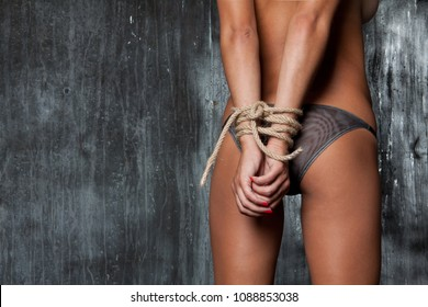 Sexy ass of a young woman with her hands tied with a rope. naked girl on a gray background