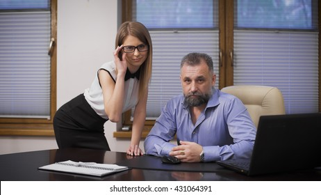Sexy assistant and her boss. The scene in the office, a respectable, gray-haired businessman and his attractive young secretary.