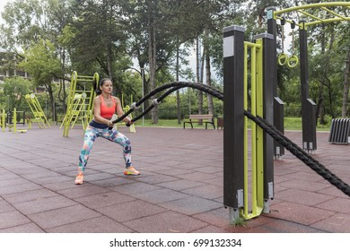 Sexy athlete girl doing heavy ropes workout in a park