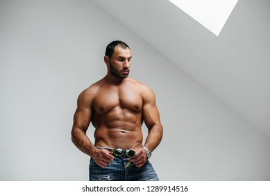 A sexy athlete with a naked torso is wearing glasses. Rest, healthy lifestyle.