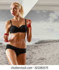 Sexy, athletic, blonde woman in the gym, against the background of the mirror, with dumbbells in hands. Sports, pumped press, a beautiful body,body Parts.
