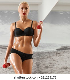 Sexy, athletic, blonde woman in the gym, against the background of the mirror, with dumbbells in hands. Sports, sportswear, health, a beautiful body, body Parts