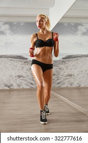 Sexy, athletic, blonde woman in the gym, against the background of the mirror, with dumbbells in hands. Sports, pumped press, a beautiful body, full-length portrait.