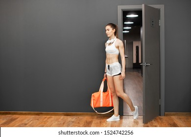 Sexy athletic girl enters the gym. Sportswoman opens the door to the locker room. Stylish black interior of modern fitness gym. Concept of health. European brunette girl holding a sports bag.