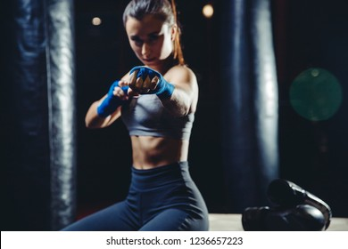 Sexy athletic girl sitting in gym between punching bags, selective focus on fist blue Boxing bandages. Dark background