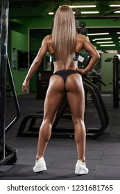 Sexy athletic girl working out in gym. Sexy butt in thong