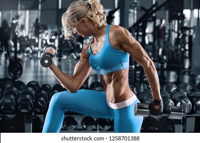 Sexy athletic girl working out in gym. Fitness woman doing exercise