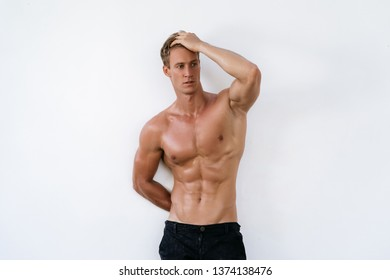 Sexy athletic man with naked torso on white background. Fashion portrait of sporty healthy guy.