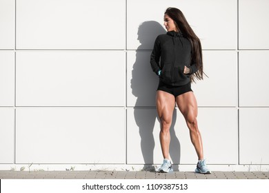 Sexy athletic woman with big quads. Muscular girl posing outdoor, muscular legs