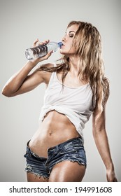 Sexy athletic woman drinking water in wet clothes on gray background