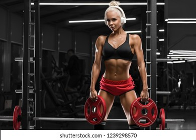 Sexy athletic woman working out in gym. Fitness girl doing exercise, muscular female