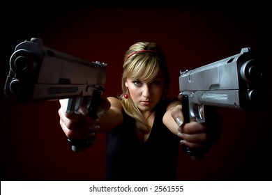 Sexy attractive blond woman with two guns aiming at camera on dark red background.