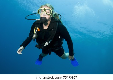 sexy, attractive, blonde girl scuba diving in clear blue water, on a coral reef in the ocean