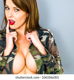 Sexy Attractive Caucasian Woman, With Brunette Hair,  Wearing An Open Military Style Army Camouflage Jacket, Posing Implied Topless Glamor Pin Up, Revealing Her Large Breasts And Cleavage