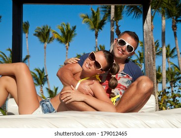 Sexy and attractive couple lying on luxury white sun bed on a tropical garden, near a swimming pool.