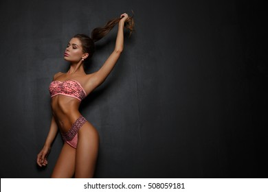 Sexy attractive girl in pink underwear (lingerie) with slim athletic tanned body is posing in the studio, dark background